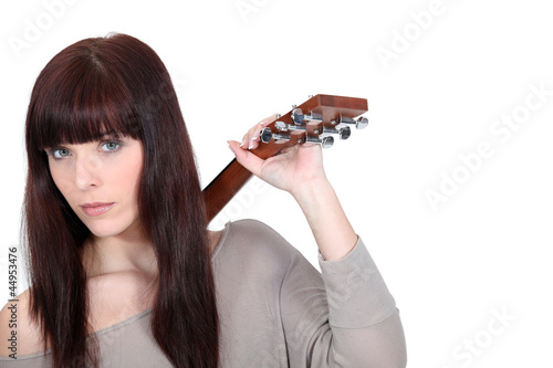 Brunette holding guitar over shoulder