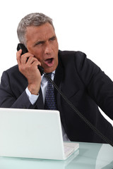Businessman yawning on the phone