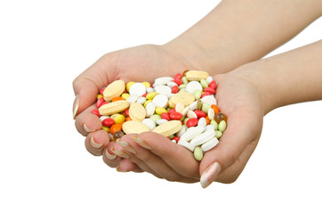 Hands holding pills on white