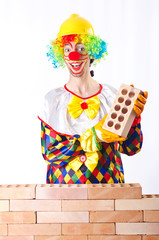 Bad construction concept with clown laying bricks