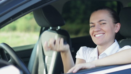 Young smiling woman with keys in a car