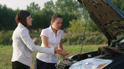 Two young women arguing in front of a broken car