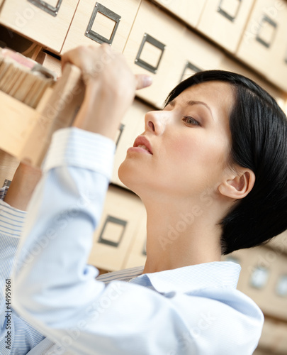 Woman seeks something in card catalog