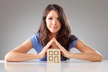 Young proudly woman make a roof with hands, symbolical
