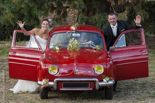 jeunes mariés et leur voiture rouge