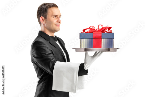 A butler with bow tie carrying a tray with gift on it
