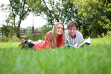 Two students reading the book on a grass in the park