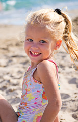 Девочка сидит на песке у моря