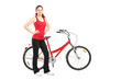 Full length portrait of a sporty girl posing next to a bike