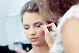 Make-up artist applying eyeshadow on outer corner of the eye