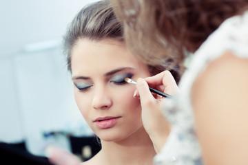 Make-up artist applying eyeshadow on outer corner of the eye