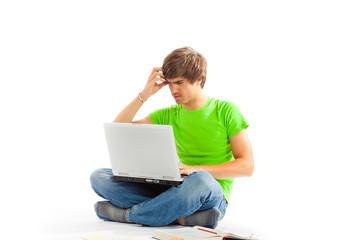 Junger Mann im Schneidersitz mit Laptop