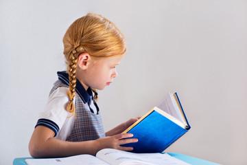 Девочка с рыжими волосами читает книгу