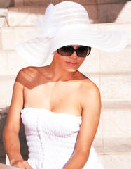 Summer woman with white dress, hat, and sunglasses