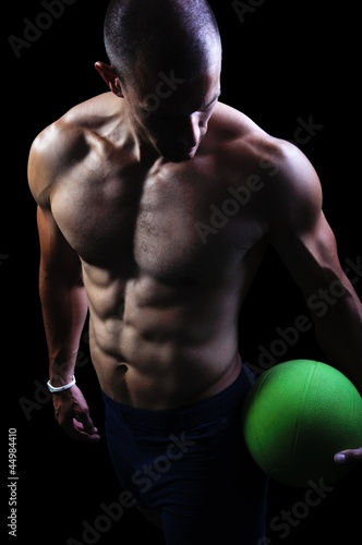 Muscular athlete man exercise on a black background