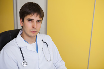 Doctor sits in yellow office