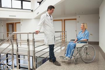 Doctor talks to nurse sitting in wheelchair