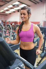 Happy Woman running on a treadmill in a gym