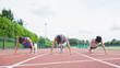 Three woman stretching on running track