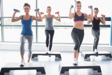 Fototapety Four women lifting weights while doing aerobics