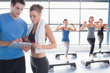 Women doing aerobics while trainer talking to woman