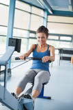 Woman training ambitiously on row machine