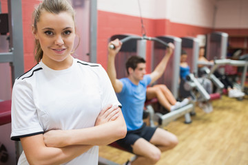 Woman with arms crossed standing in a fitness studio