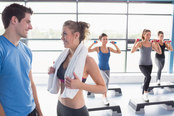 Aerobics class lifting weights while woman talking to trainer