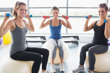 Smiling women lifting weights on an exercise ball