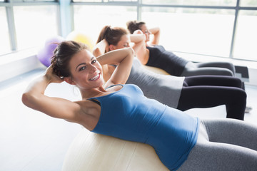 Three women doing sit-ups