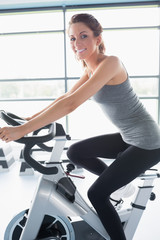 Smiling woman riding an exercise bike