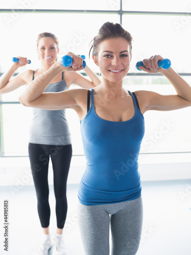 Smiling woman lifting weights