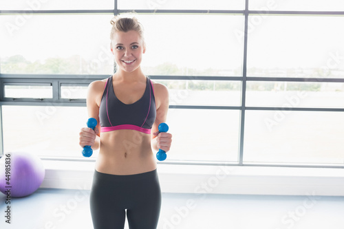 Woman lifting weights in fitness studio