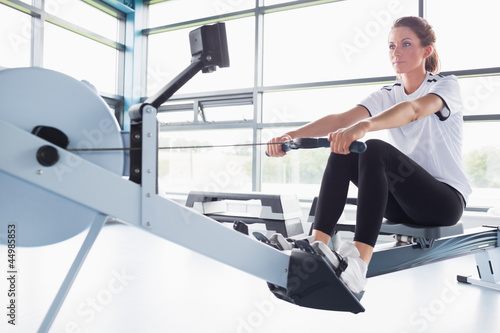 Concentrating  woman training on row machine