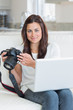 Brunette holding a camera and a laptop