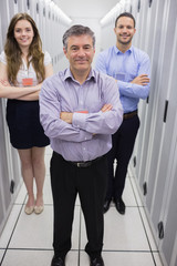 Smiling technicians standing in data center