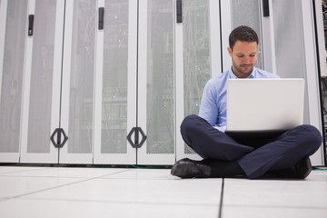 Technician sitting on floor working on laptop