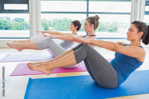 Women at yoga class in boat pose