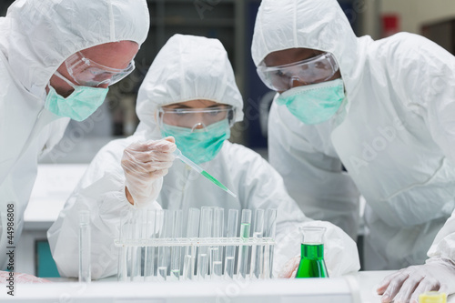 Chemist adding green liquid to test tubes with two other chemist