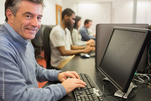 Smiling man sitting in front of the computer