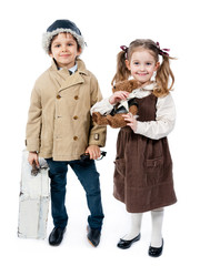 Sweet little girl with teddy bear and boy with case in retro sty