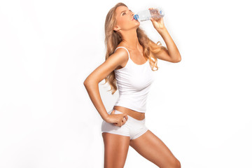 Blond woman drinking water from battle. Studio white.