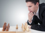 business man playing chess, making the move