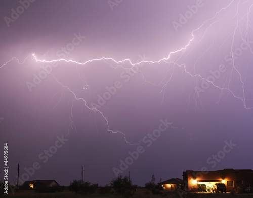 A Lightning Bolt Streaks Above a Neighborhood