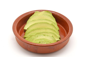 avocado cut into clay bowl
