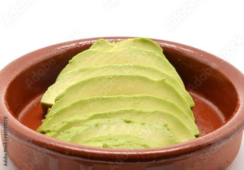 avocado cut into clay bowl