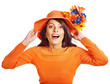 Woman wearing orange sweater and hat.