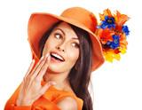 Woman wearing orange hat with flower.