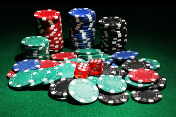 Dices and chips for poker on green table