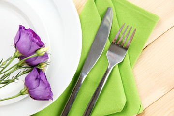 Tableware with flower on bright napkin close-up